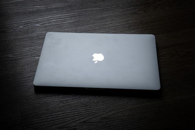 zaklapnutý počítač na černém stole ze dřeva